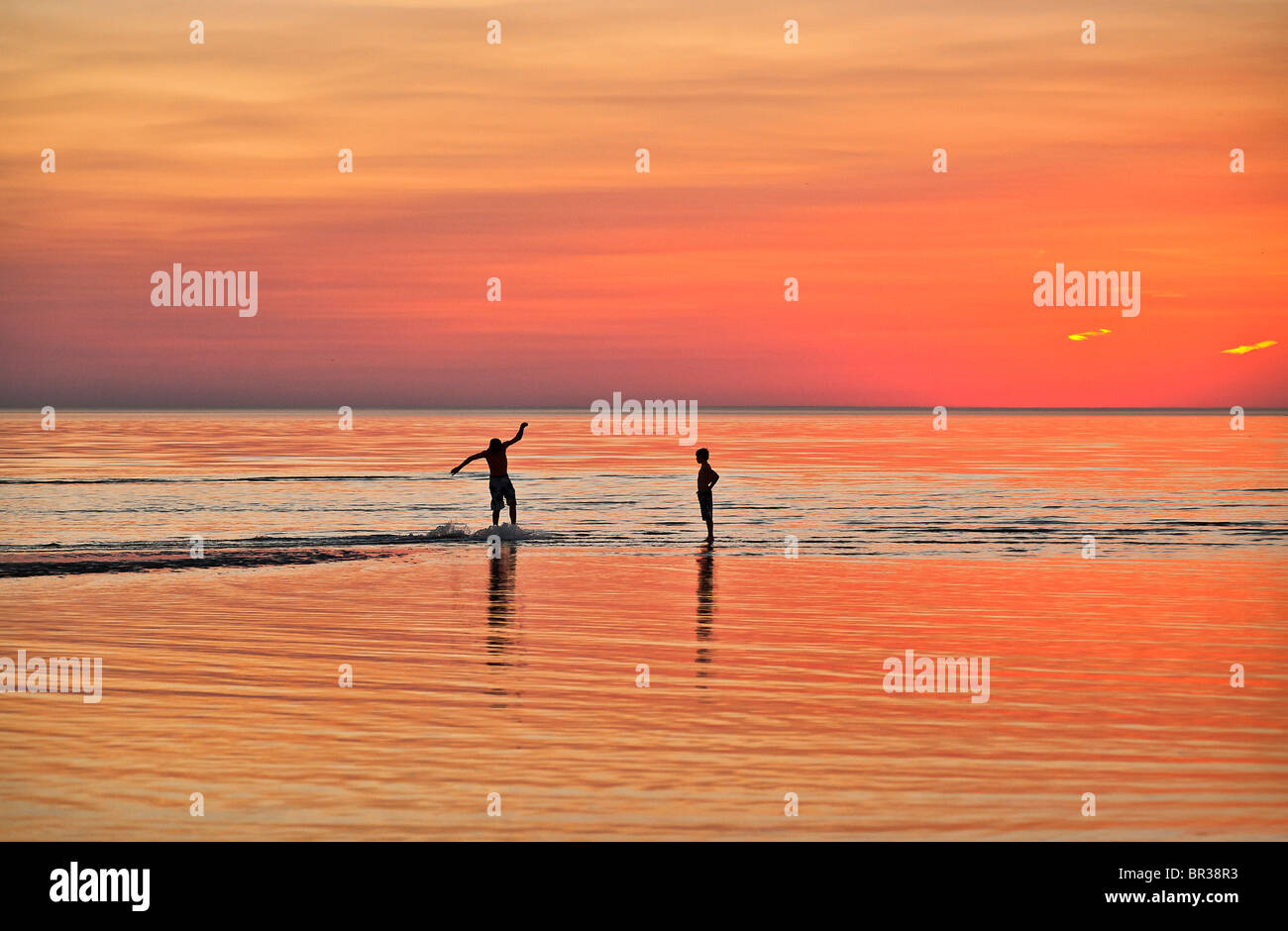 Boys boogie boarding in shallow water, Cape Cod, Massachusetts, USA - Stock Image