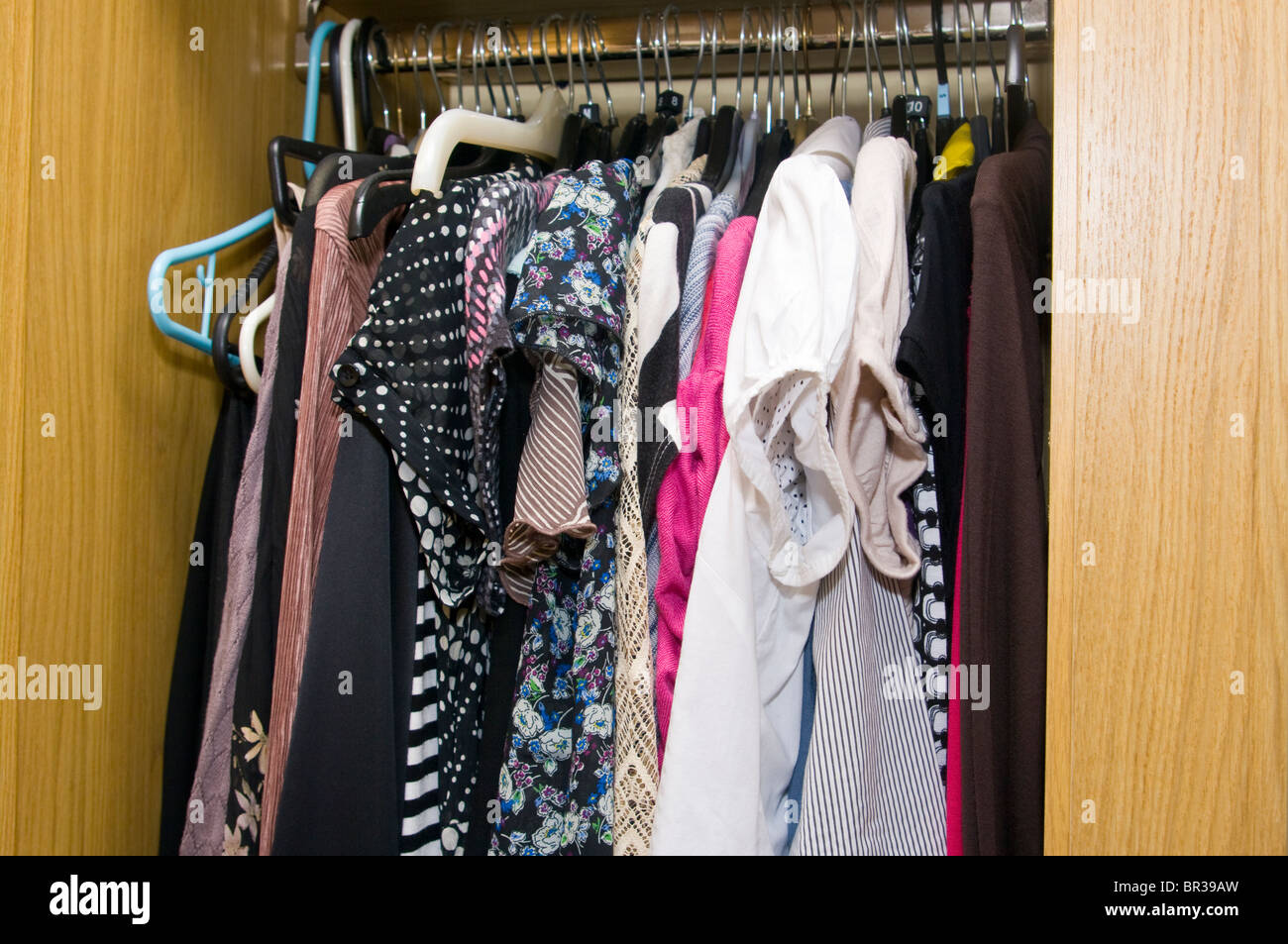 Womans Clothes On Hangers In An Open Wardrobe - Stock Image