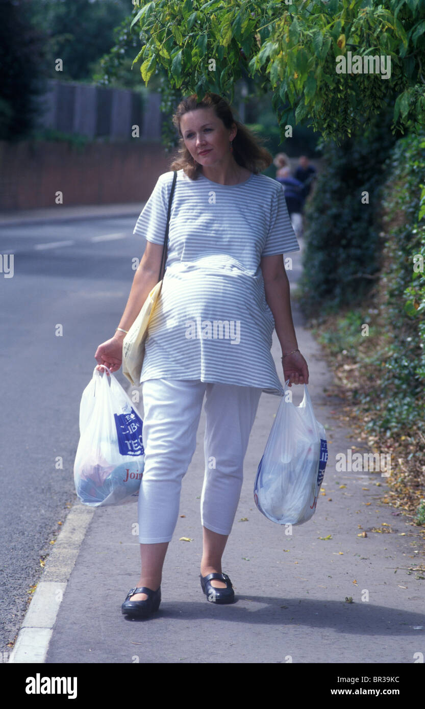 heavily pregnant woman walking down the street carrying bags of shopping - Stock Image