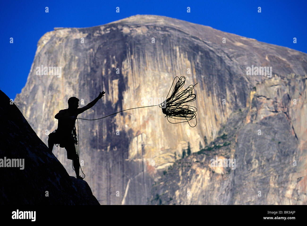 Silhouette against a granite dome of a climber throwing a rope off a cliff. - Stock Image
