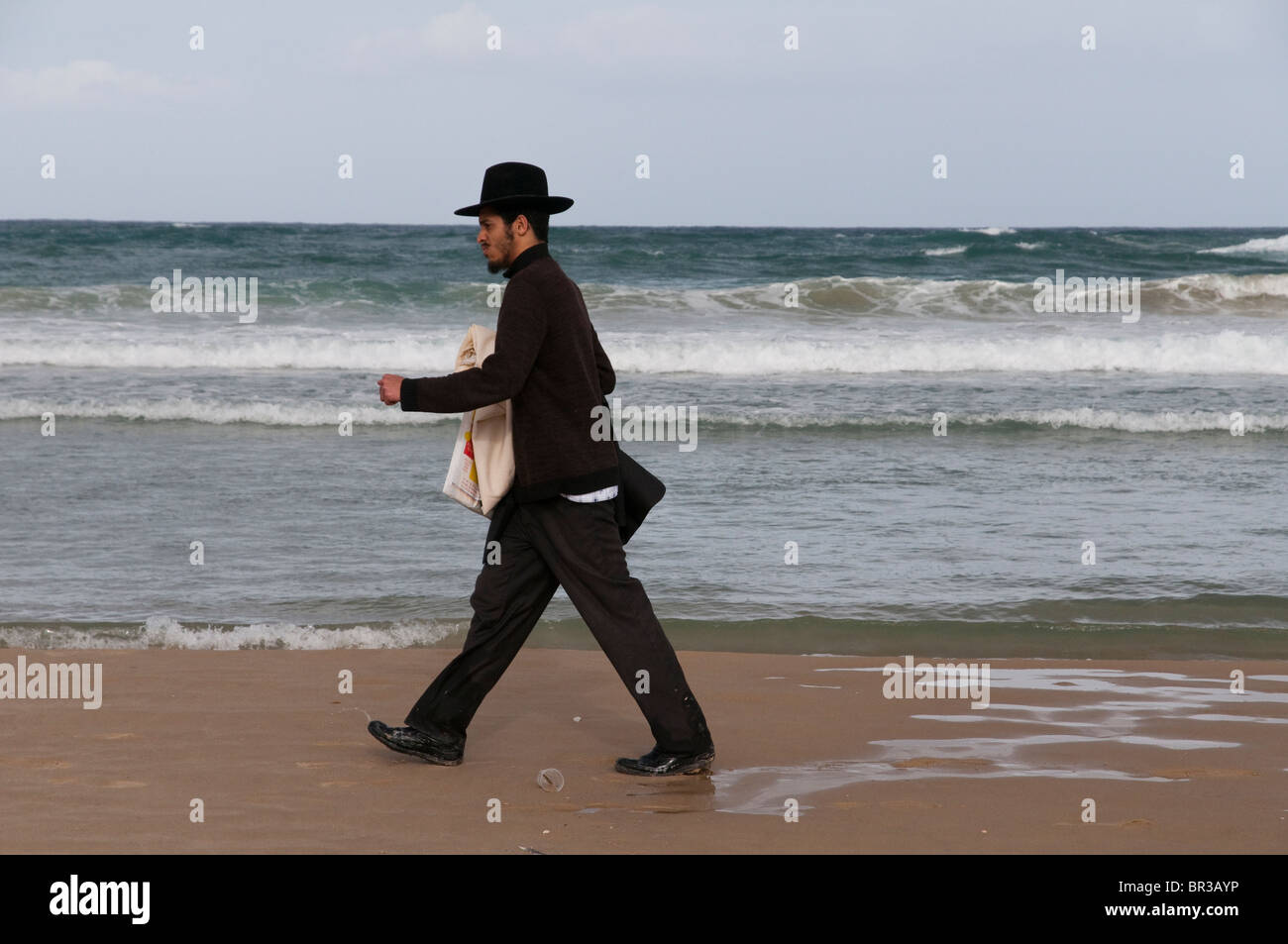 orthodox jew walking on the beach in tel aviv. Israel - Stock Image