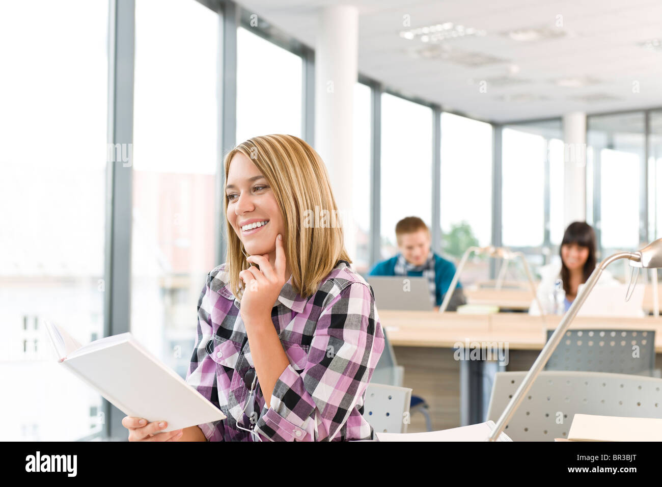 Happy female student with book in classroom, schoolmates in background - Stock Image