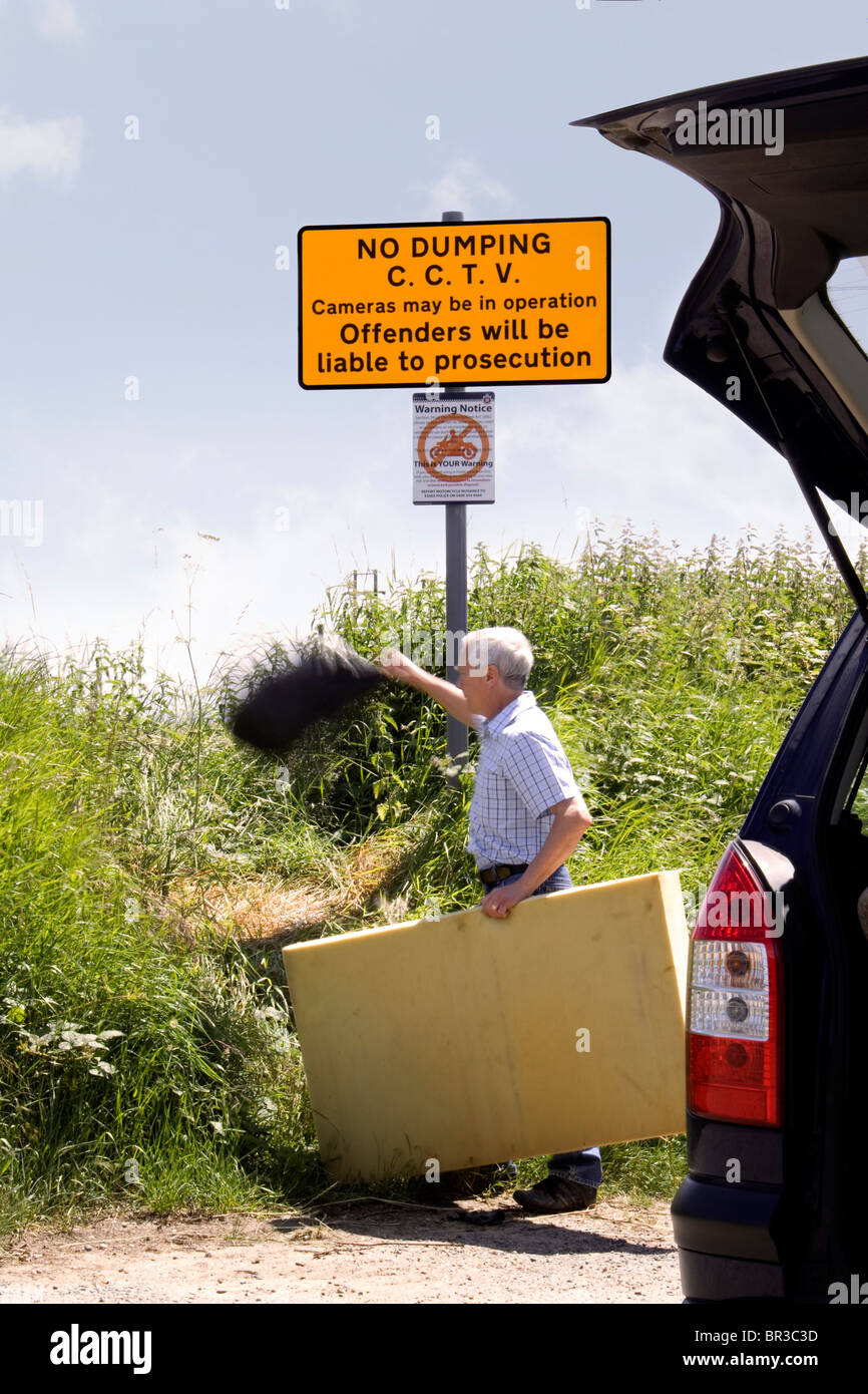 A man throwing a bag of rubbish in a country lane under a 'no dumping' sign which states that CCTV cameras - Stock Image