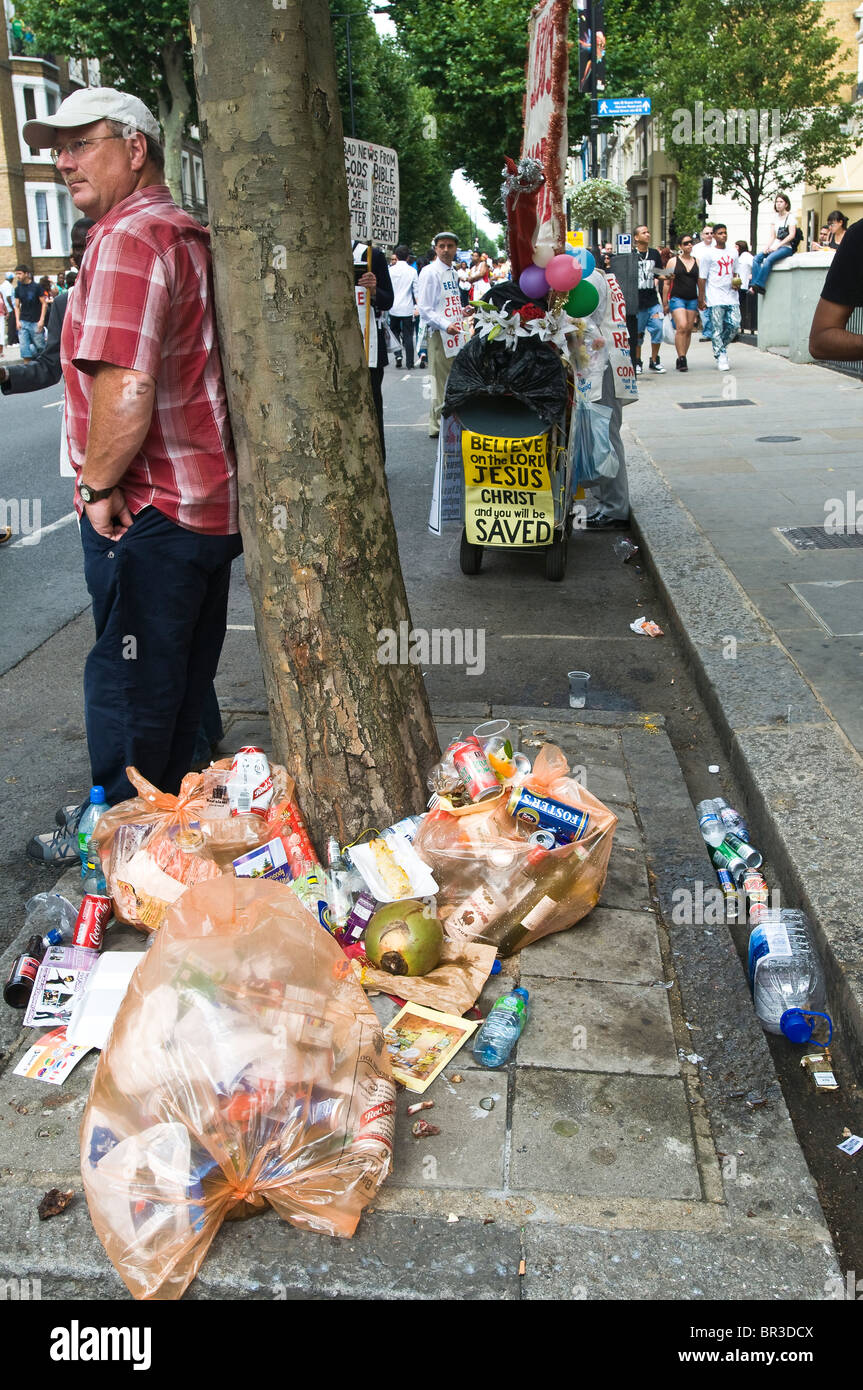 A man leaning against a tree amidst rubbish piling up at the 2009 Notting Hill Carnival Stock Photo