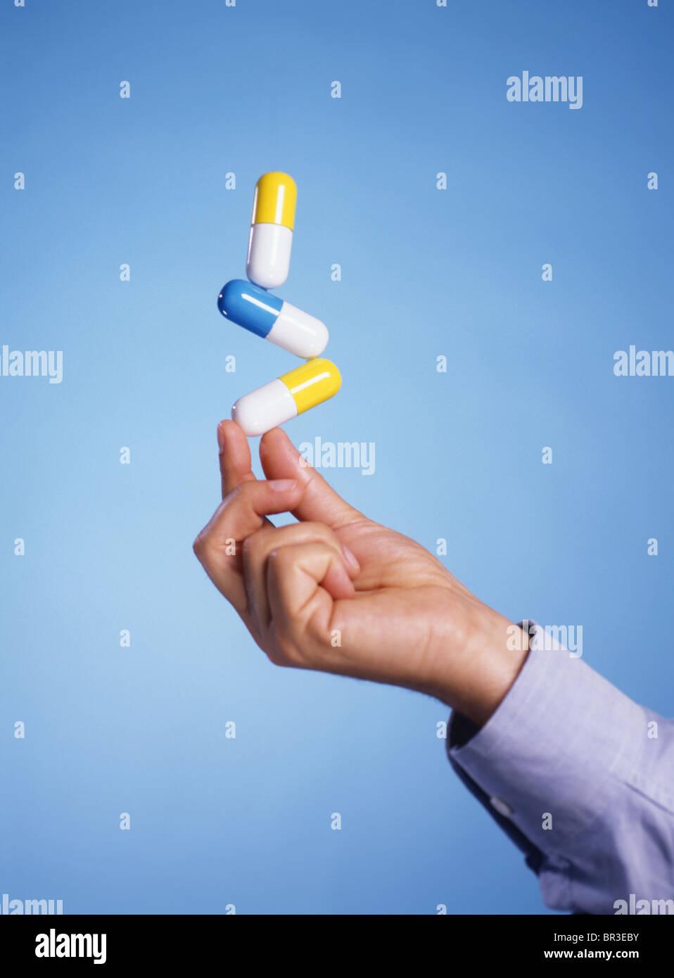 man balances pills - Stock Image