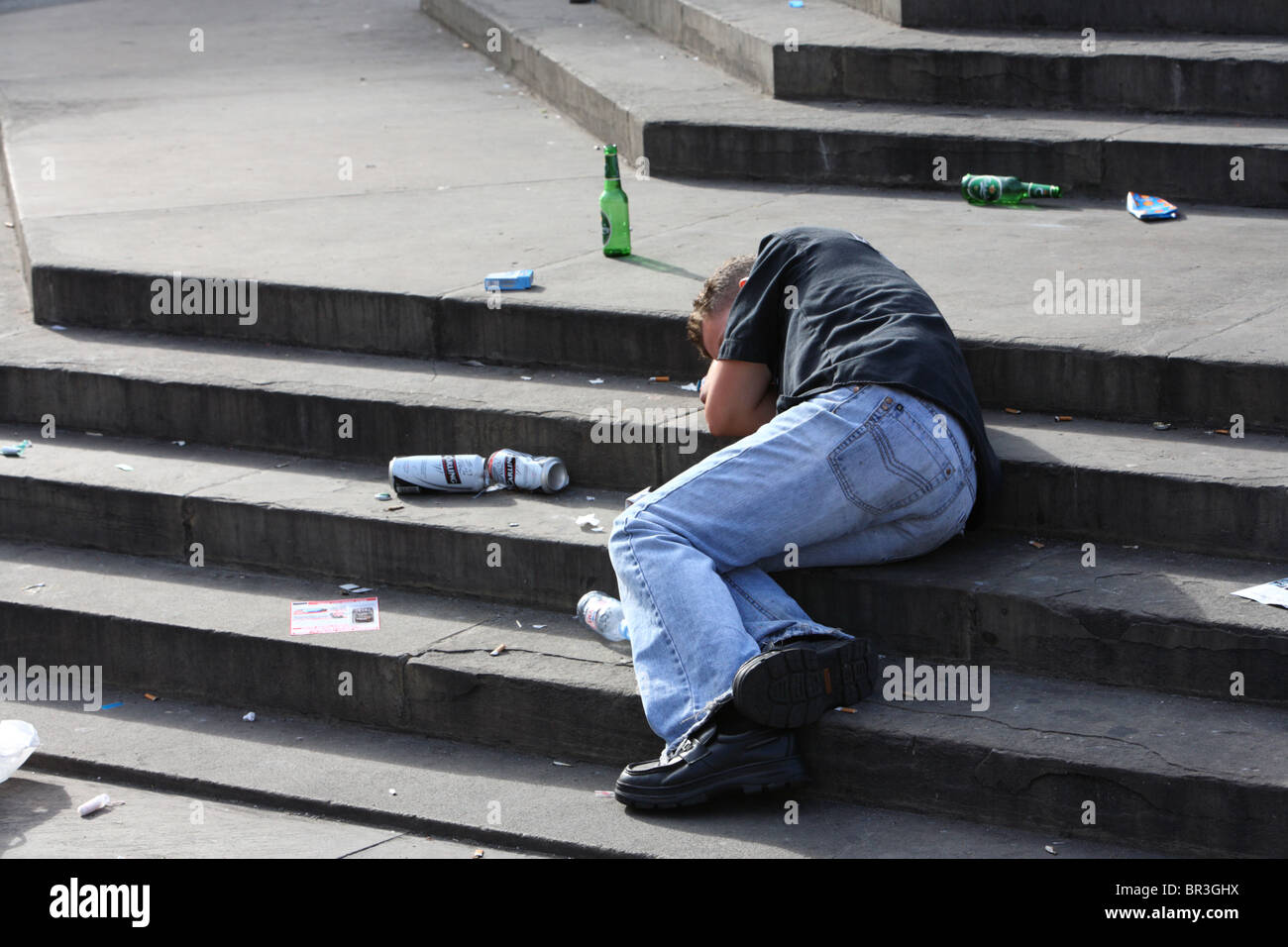 Young man lying asleep on the steps of Eros after drinking alchohol, Piccadilly Circus, Westminster, London, W1. - Stock Image