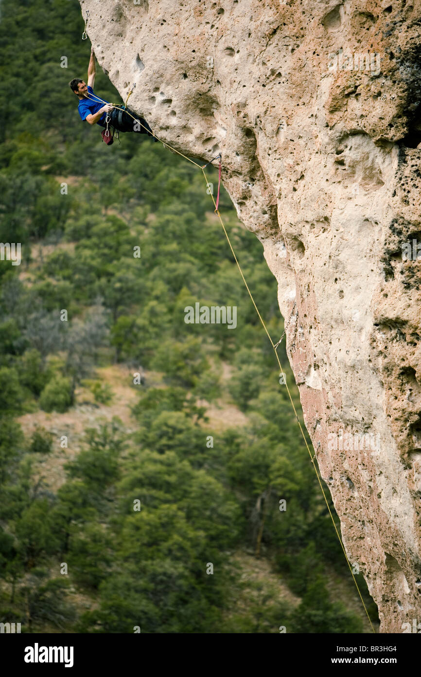 A man clipping a bolt while sport climbing and overhanging prow. - Stock Image
