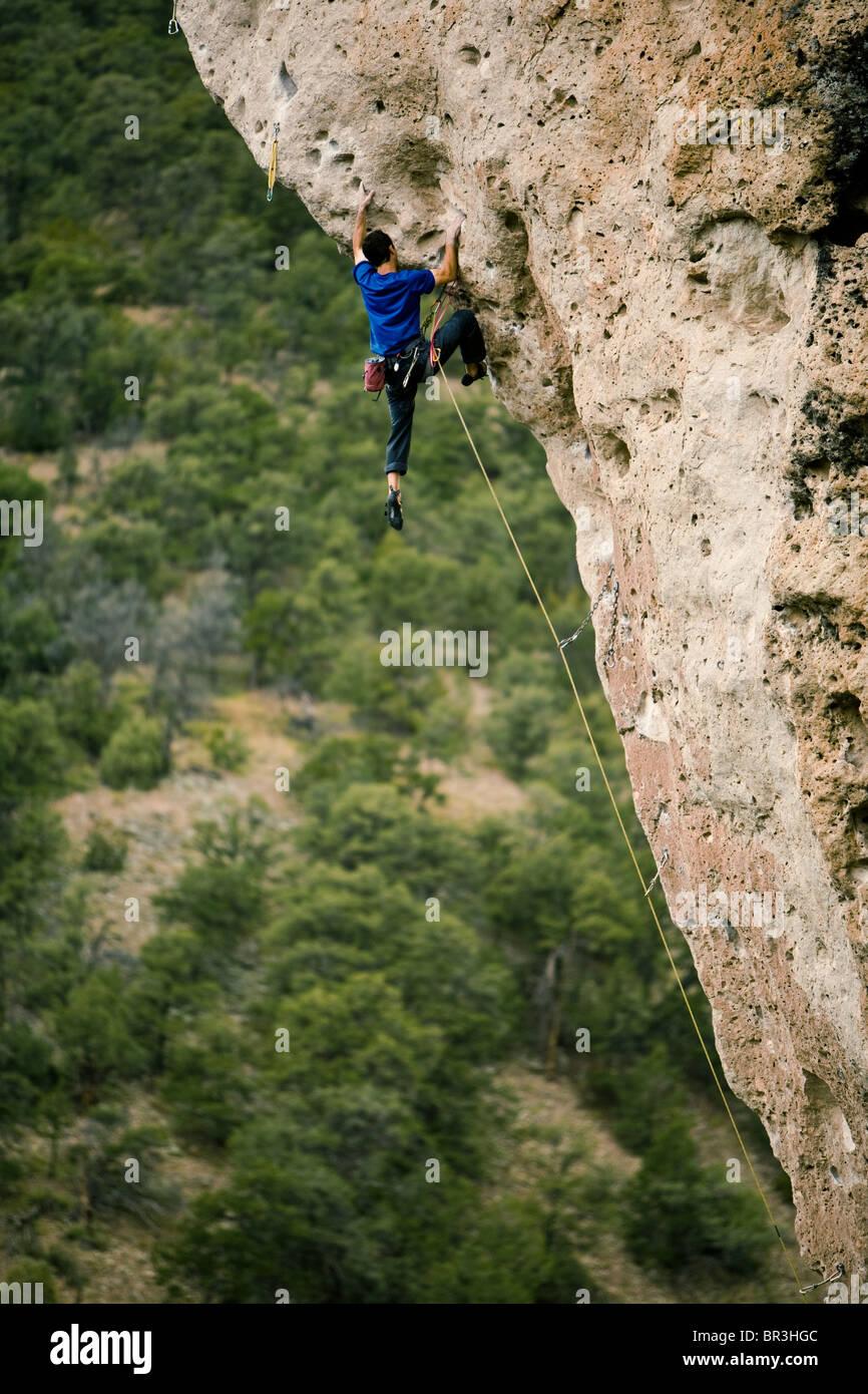 A man rock climbing an overhanging prow. - Stock Image