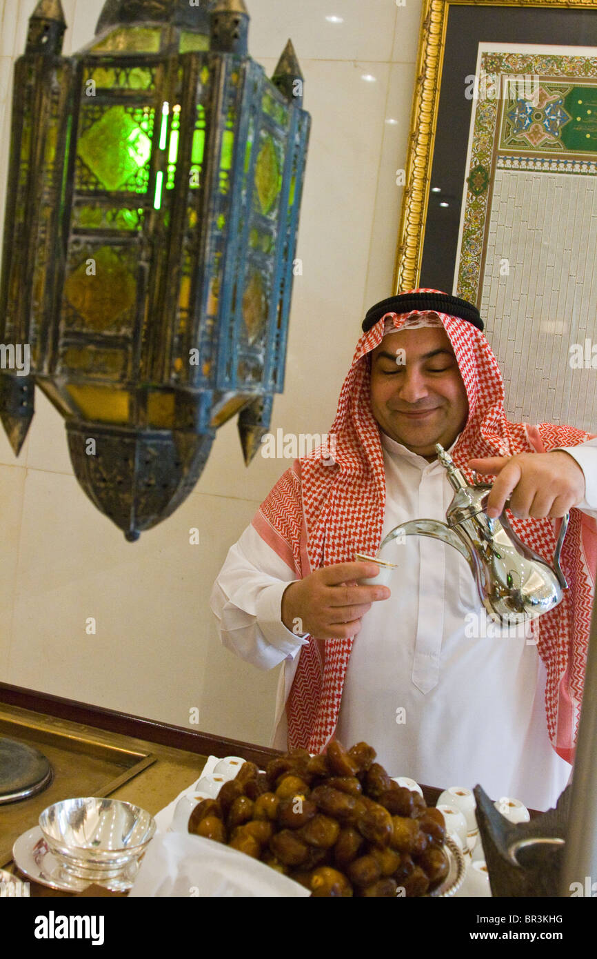Arab man offering hospitality with tea and dates in Kuwait City, Kuwait - Stock Image