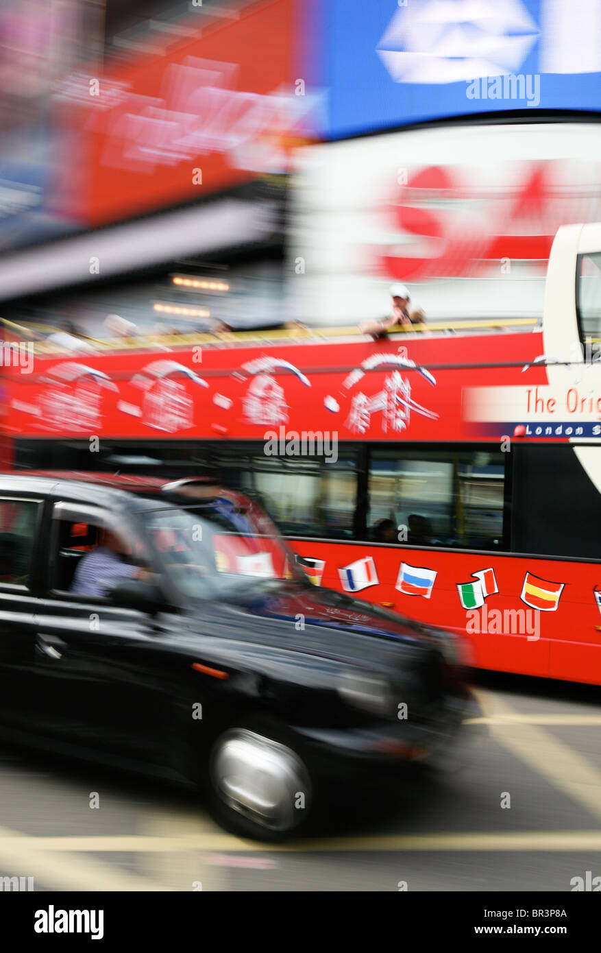 Taxi and sightseeing bus travelling through Piccadilly Circus, London - Stock Image
