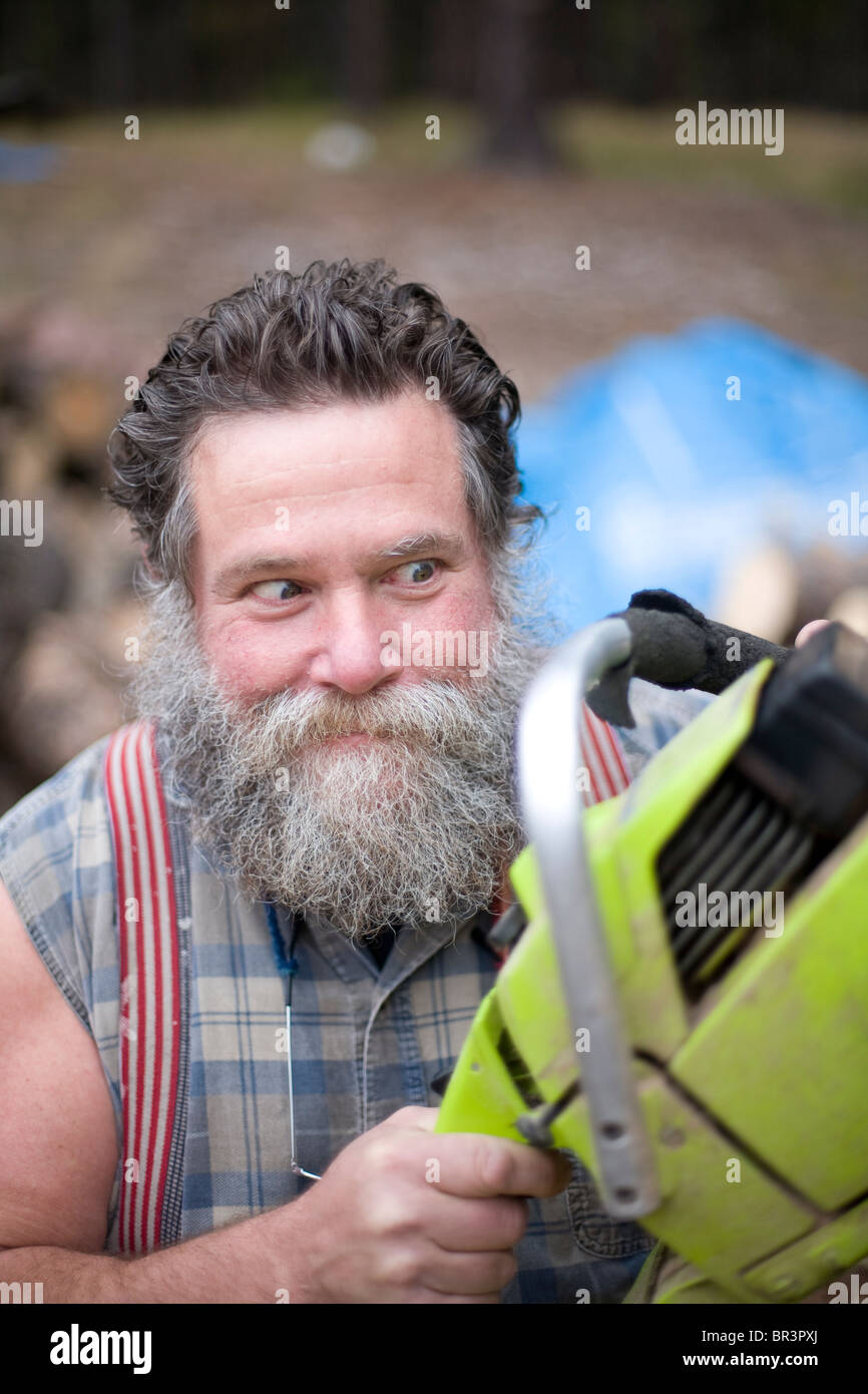 Crazed looking man with chainsaw. Stock Photo