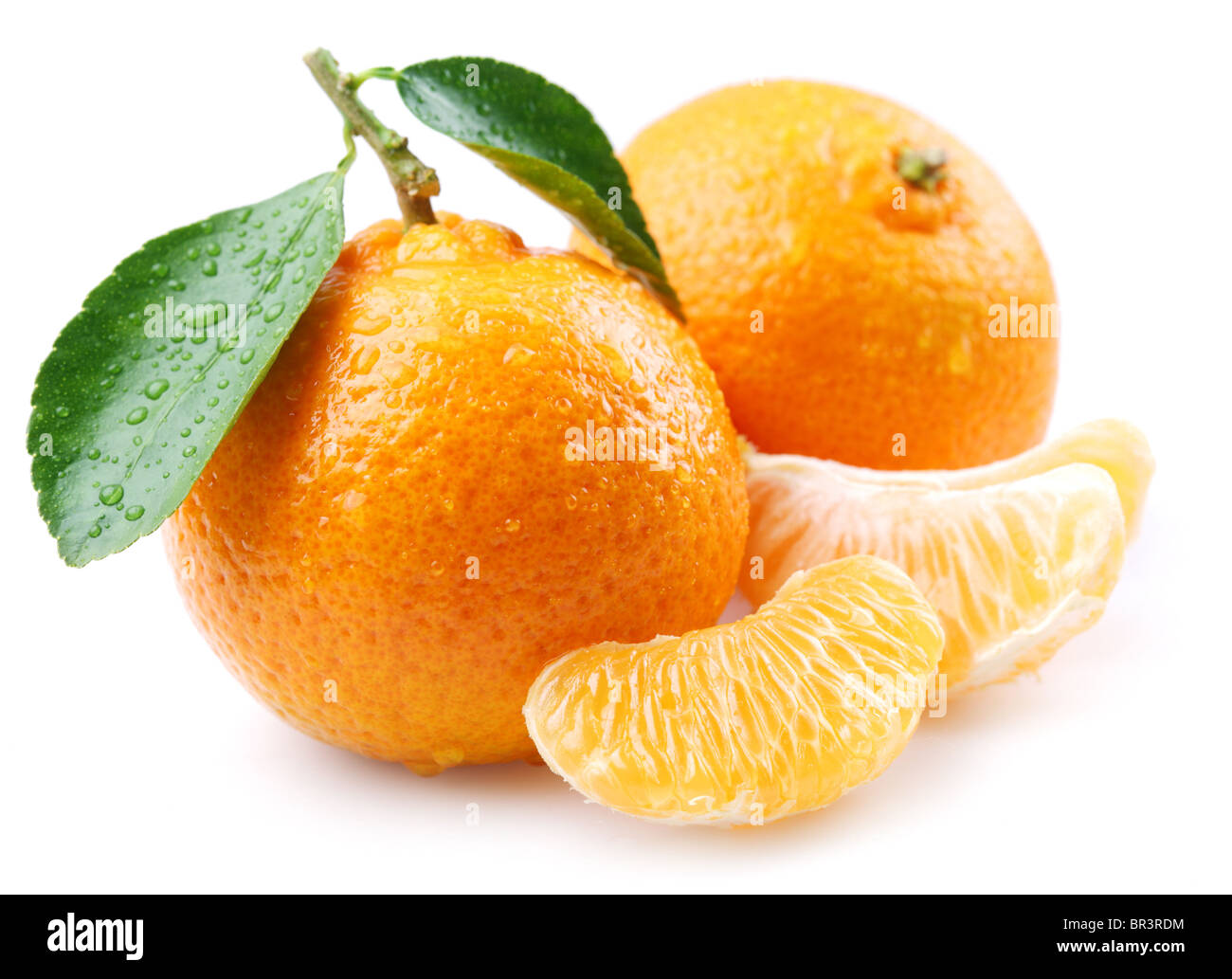 Ripe tangerines with leaves and slices on white background - Stock Image