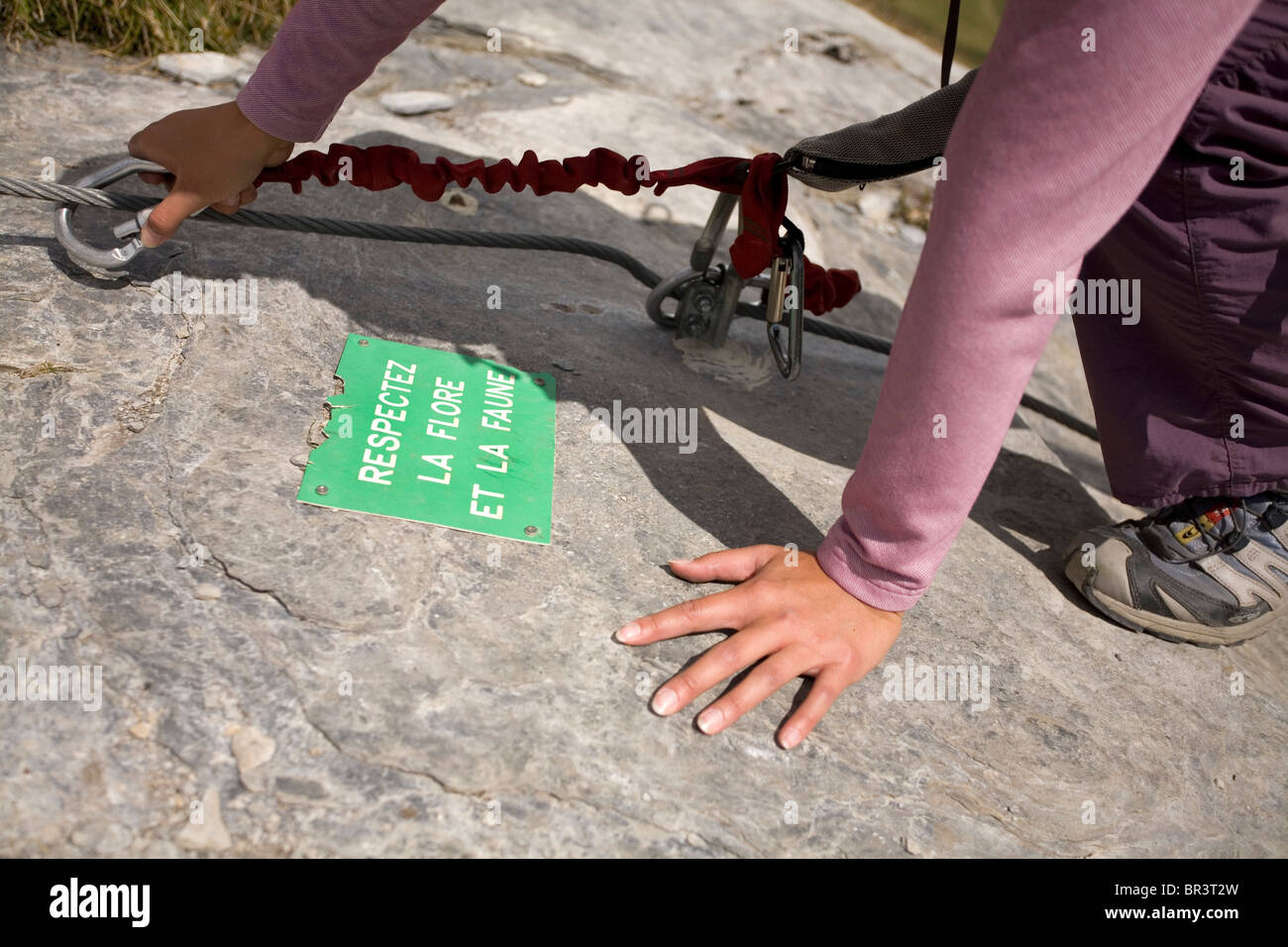 A young woman attaches herself to the cable bolted to the rock while engaging in the sport of Via Ferrata in the - Stock Image