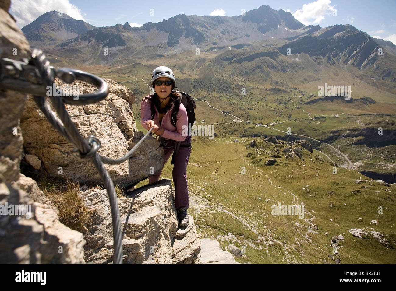 A young woman uses the cable bolted to the rock for climbing support while engaging in the sport of Via Ferrata - Stock Image