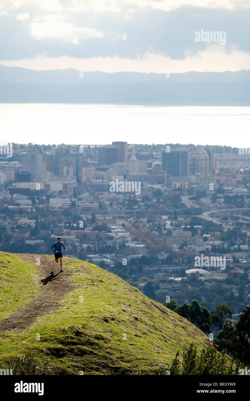 Man trail running above a city. - Stock Image