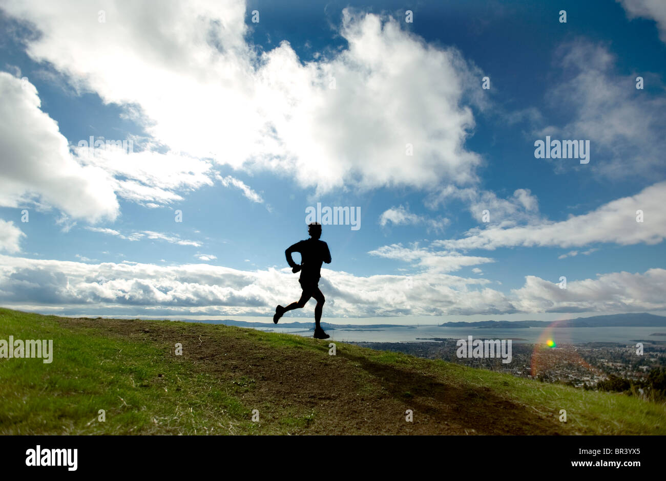 Silhouette of a man trail running above a city. - Stock Image