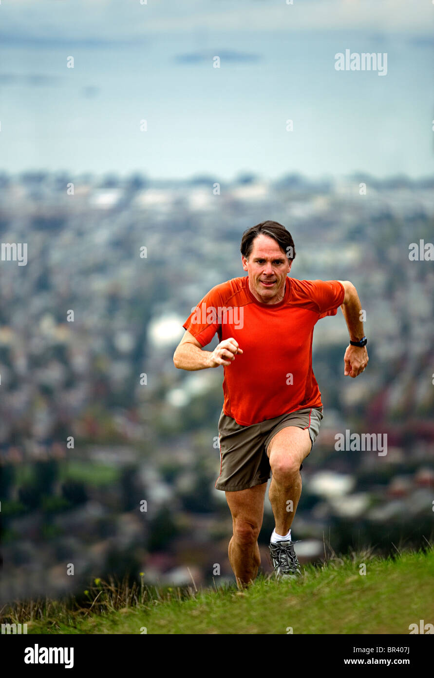 Man trail running on a hill above a city. - Stock Image