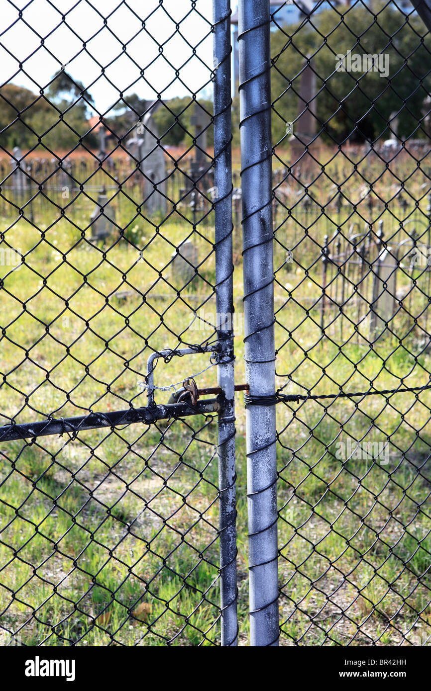 Locked Cemetery gate with gravestones in the distance - Stock Image