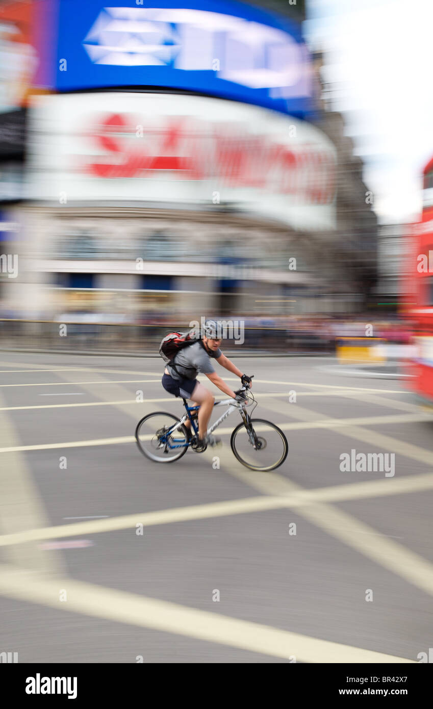 Cyclist at speed in Piccadilly Circus, Central London - Stock Image