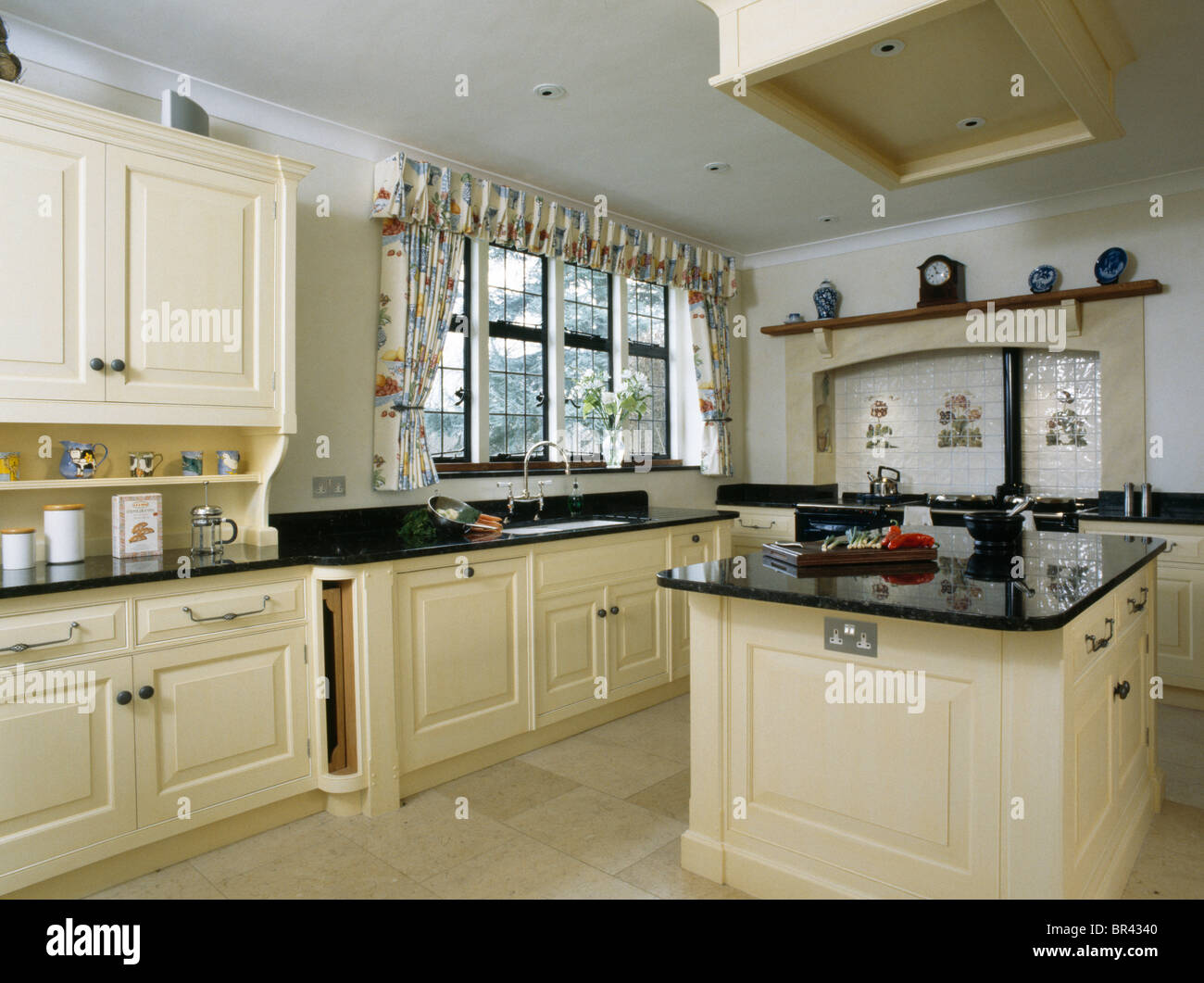 cream fitted island unit with granite worktop in large white countrycream fitted island unit with granite worktop in large white country kitchen with floral curtains at the window