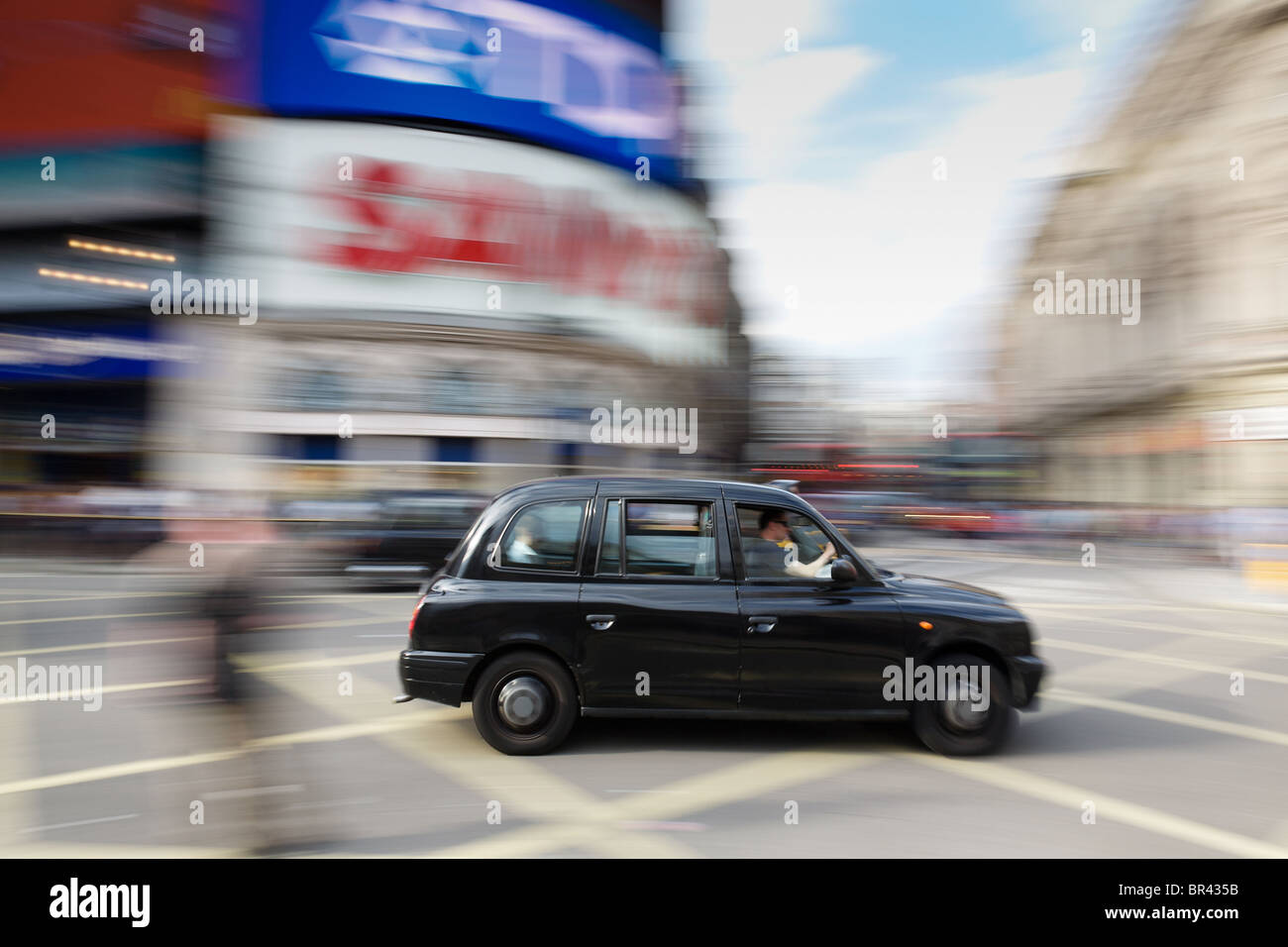 London taxi at speed through Piccadilly Curcus, London - Stock Image