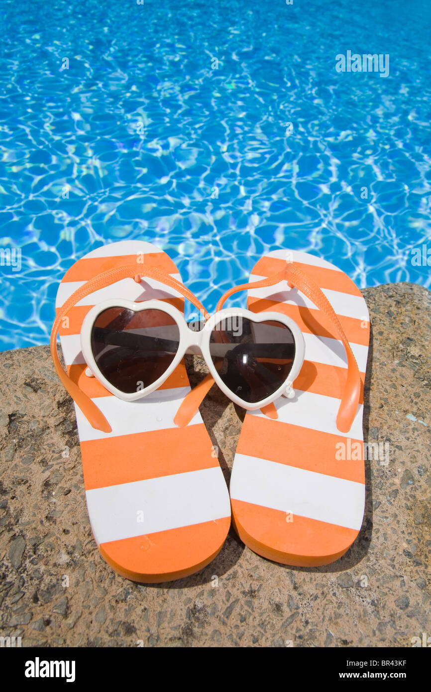 0fa94169438a Striped flip flops and heart shaped sunglasses by the pool Stock ...