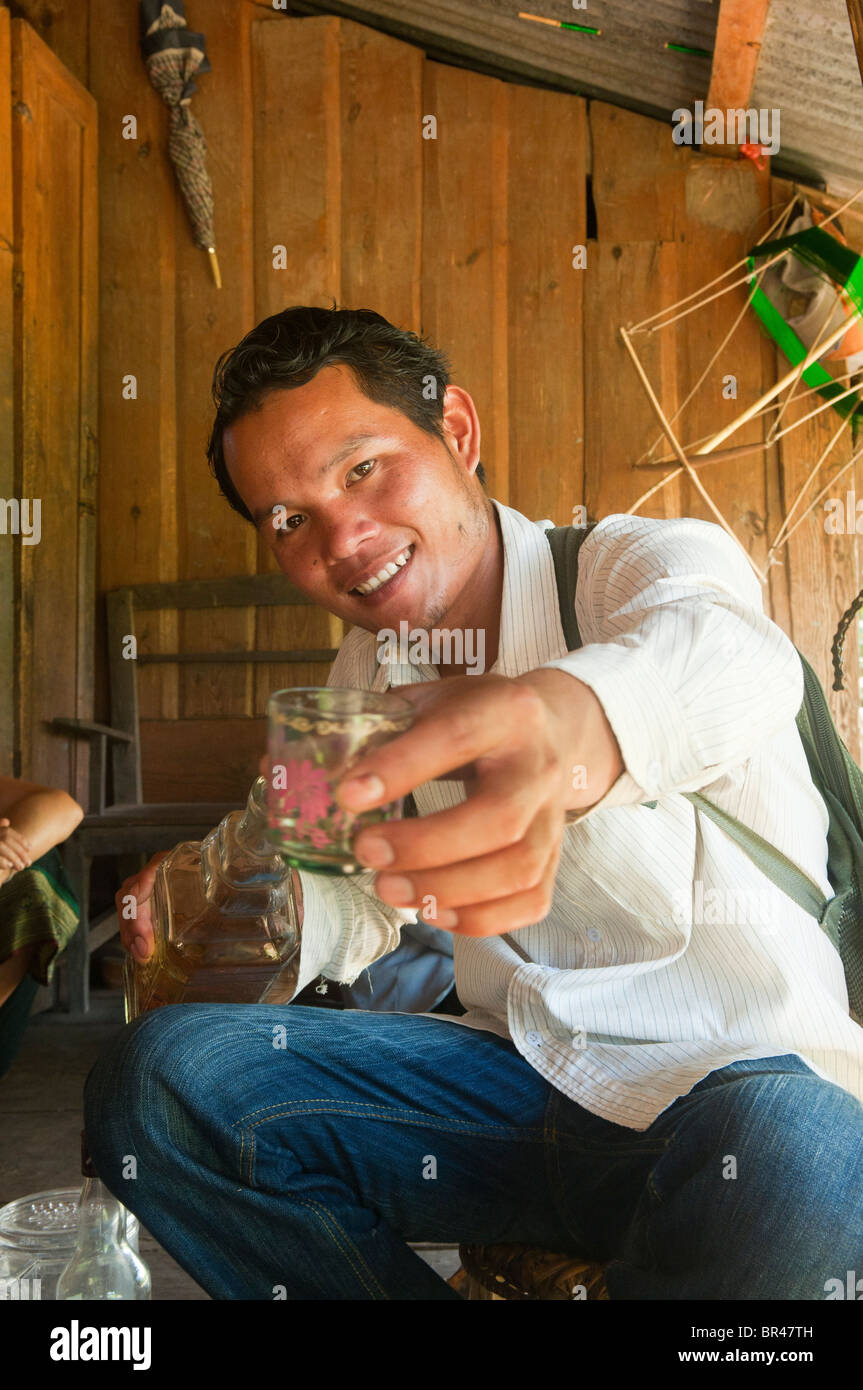 drinking a Lao whiskey toast on the Plain of Jars in Laos - Stock Image