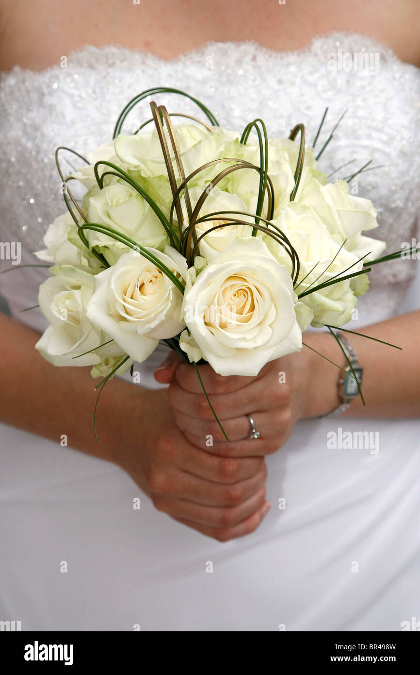 A bride holds a bouquet of white flowers on her wedding day - Stock Image