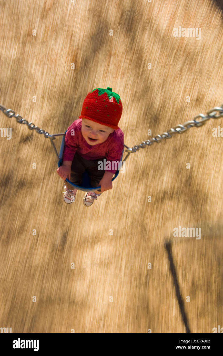 Toddler in swing at town  park, Durango, Colorado (blurred motion). - Stock Image