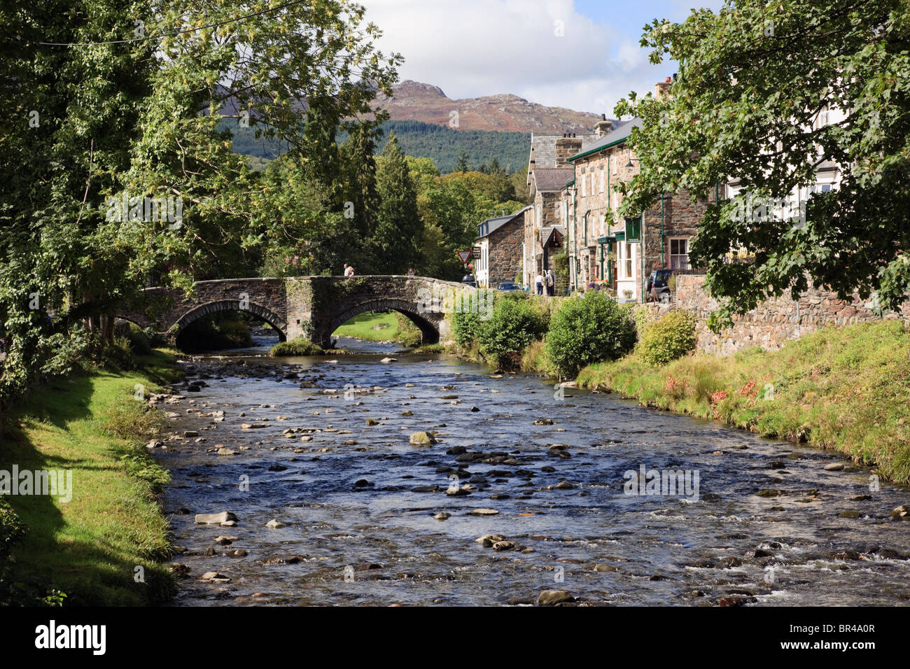 Beddgelert, Gwynedd, North Wales, UK, Europe. View along Afon Colwyn River to the old arched bridge in the village - Stock Image