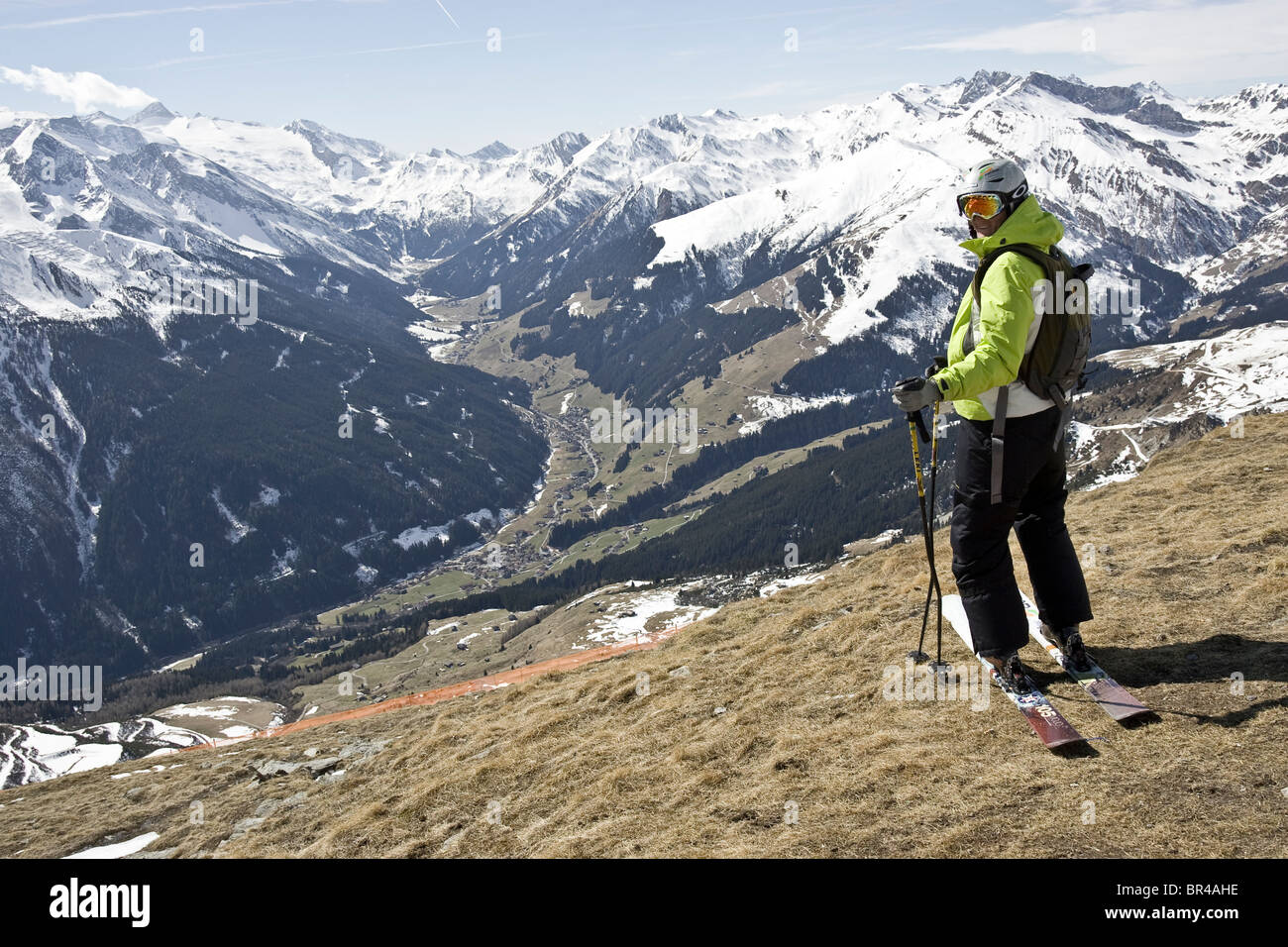 A man pauses at the top of a snowless ski trail in Mayrhofen, Austria. - Stock Image