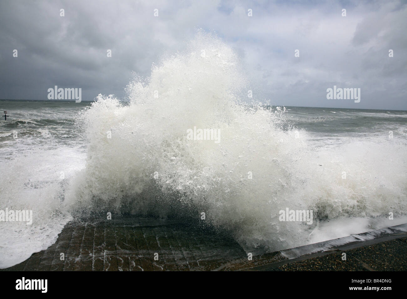 Stormy sea waves crashing against a sea wall on the Norfolk coast. - Stock Image