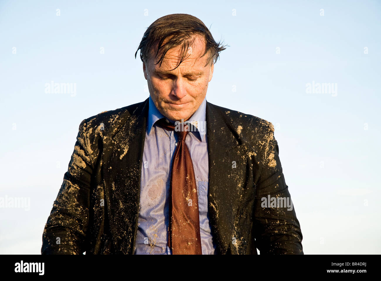 A depressed businessman is soaking wet - Stock Image