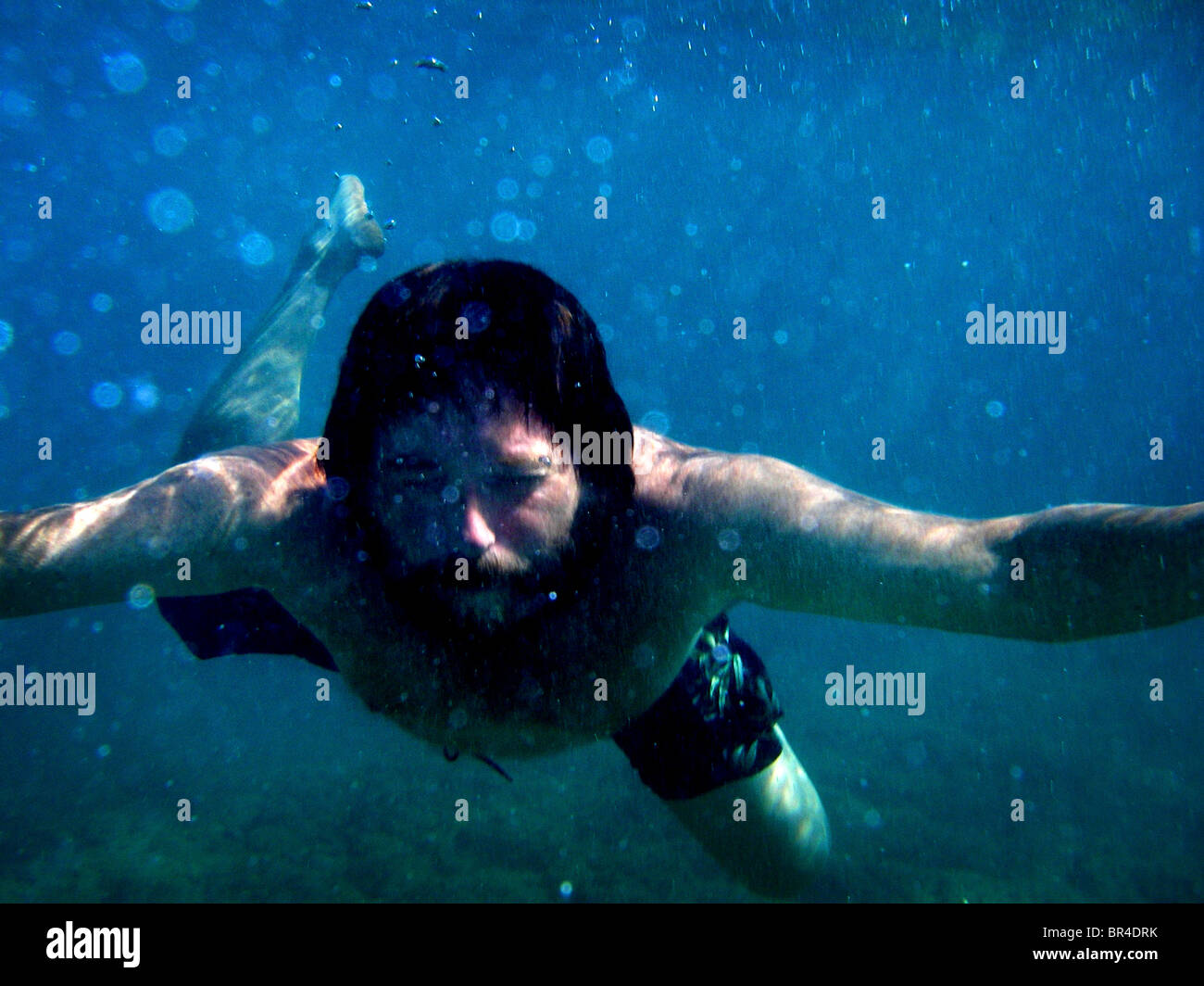 A man floats underwater at Halona Beach Cove in Hawaii. - Stock Image