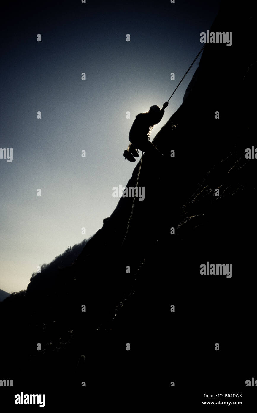 Silhouette of a young man rappelling down a cliff face in Cashiers Valley, North Carolina. - Stock Image