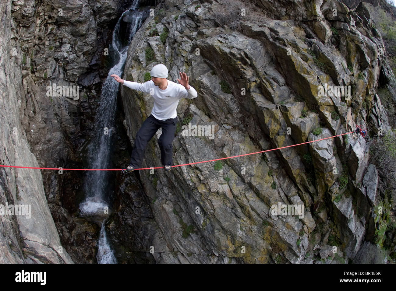 man slacklining over a waterfall and rock gorge, Wasatch Mountain, Utah - Stock Image
