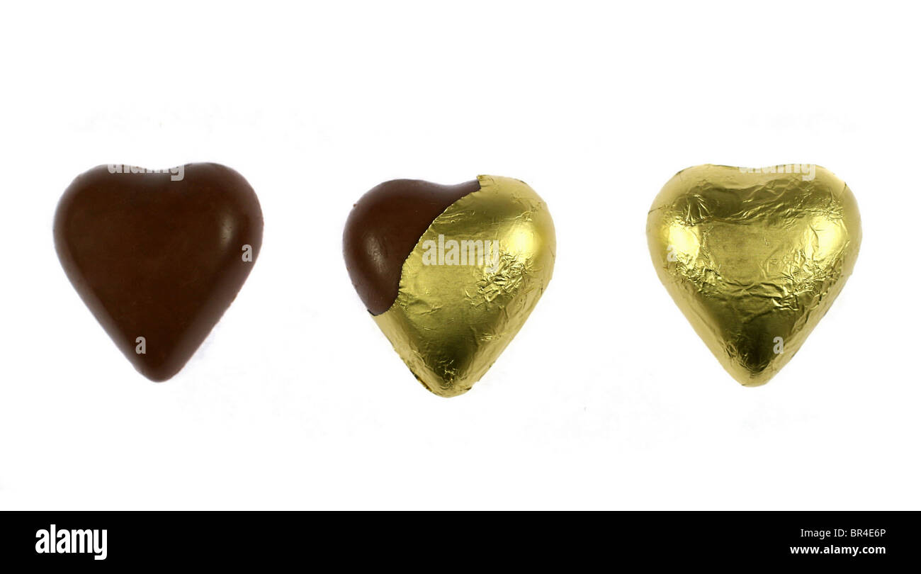 Three wrapped and unwrapped chocolate hearts isolated on white - Stock Image