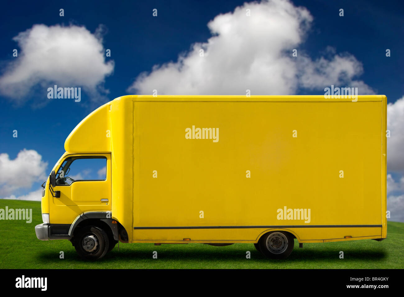 Yellow truck on a beautiful green meadow with copy space for text Stock Photo