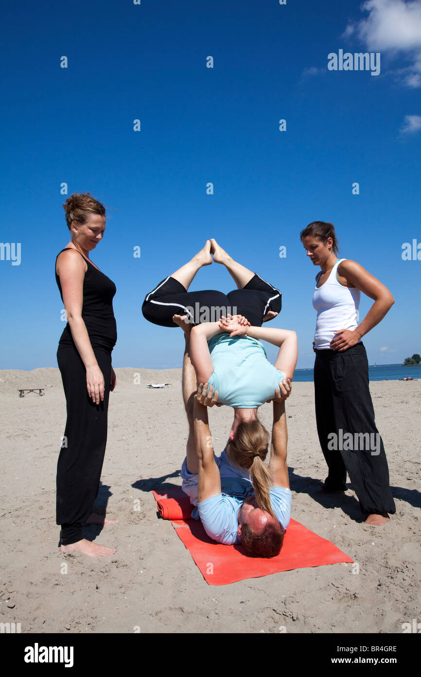 People practicing acroyoga on the beach Blijburg in Amsterdam, the Netherlands. Acroyoga is a special, acrobatic Stock Photo