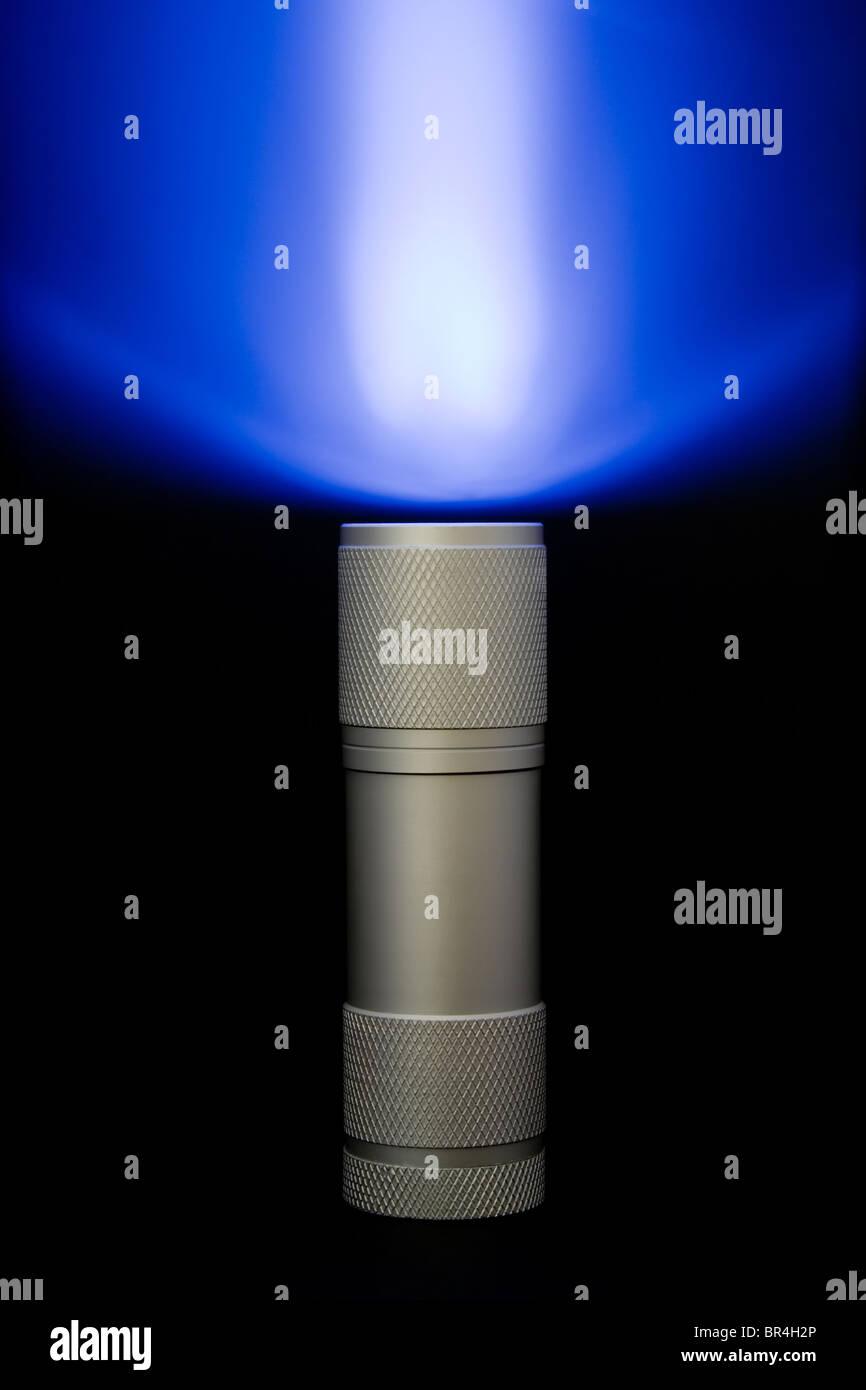 Pocket flashlight with beam in the haze - Stock Image