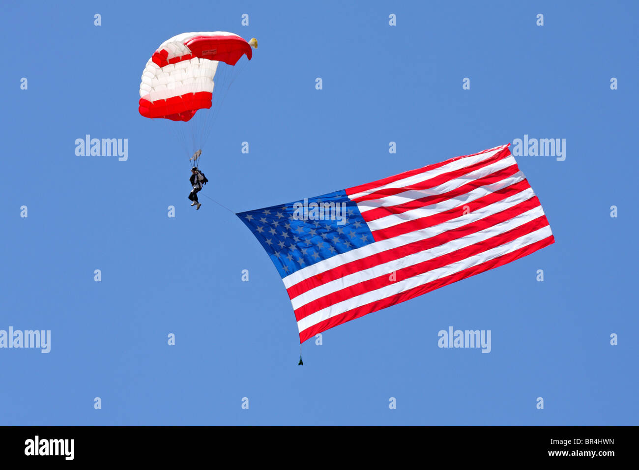 The stars and stripes makes its way down to earth beneath the canopy of a parachutists. - Stock Image