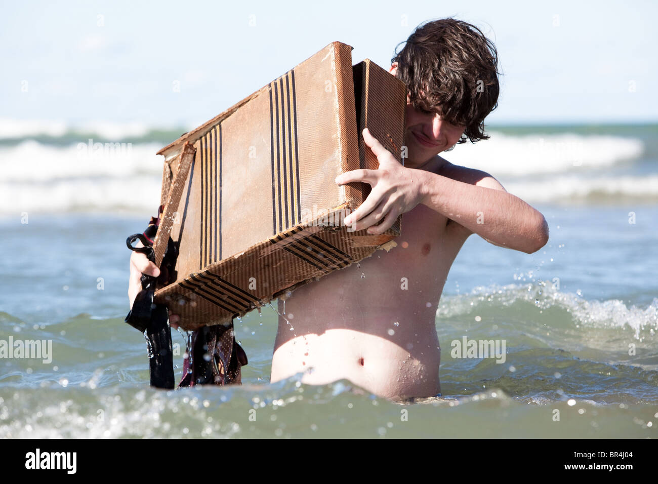 A boy carries his we suitcase - Stock Image