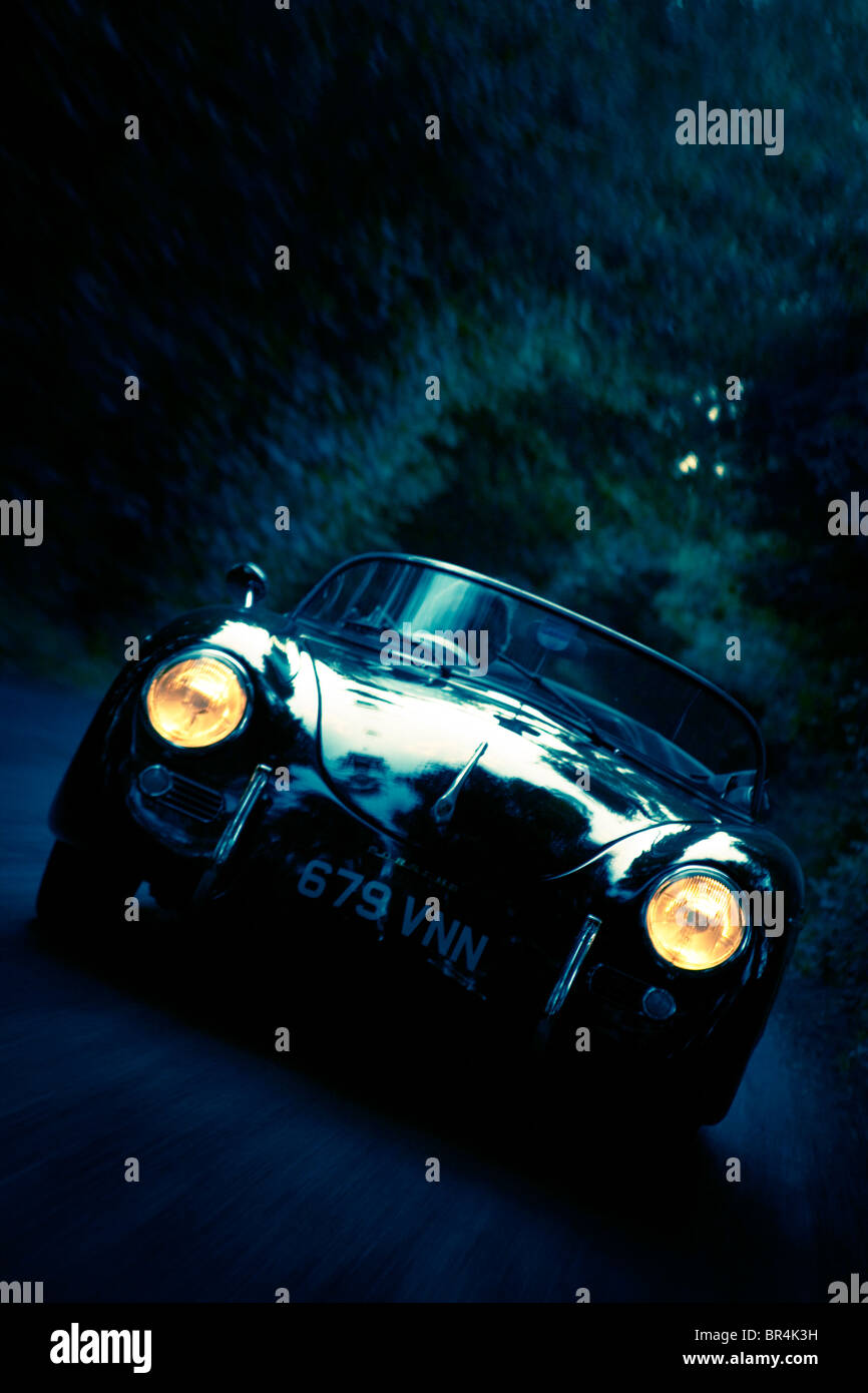 Sports car driving along country road Stock Photo