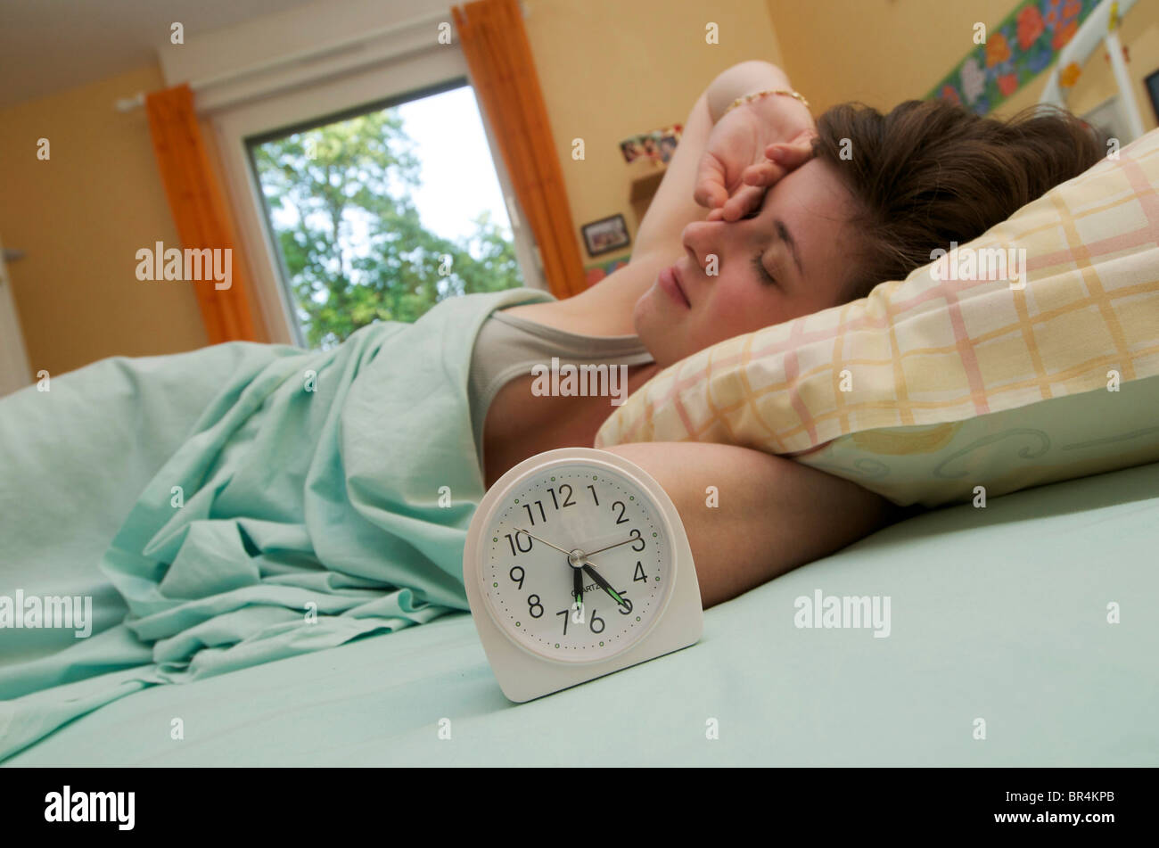 Young woman with alarm clock waking up early in her bed and rubbing her eyes - Stock Image