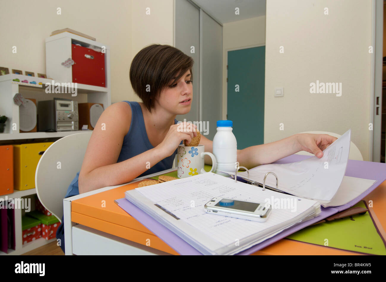 Student studying / revising in her university / college apartment with her breakfast - Stock Image