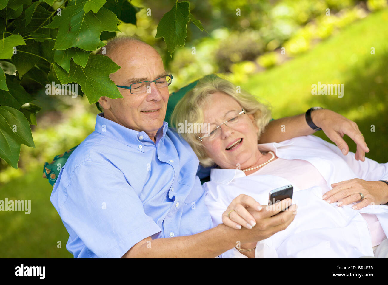 Happy senior couple smartphone in garden Stock Photo