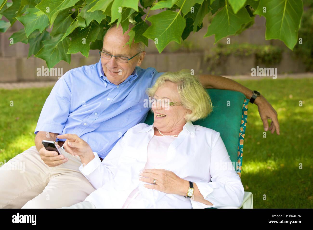 Happy senior couple smartphone in garden Stock Photo