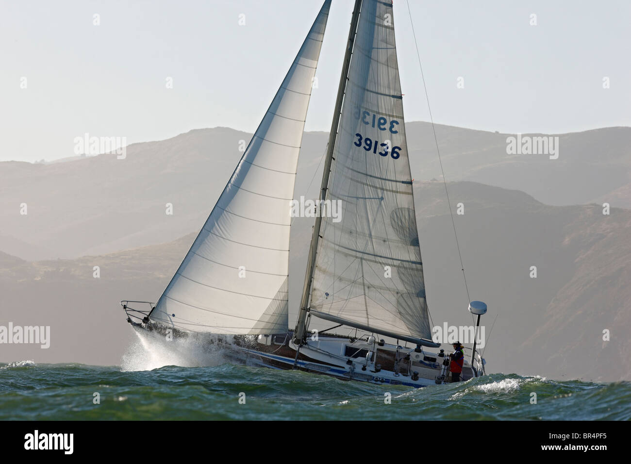 A sailor singlehands his 39-foot sailboat in heavy weather off the California coast. - Stock Image