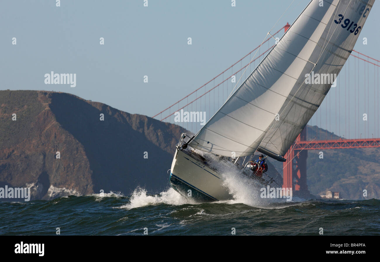 A sailor singlehands his 39-foot sailboat in heavy weather past the Golden Gate Bridge. - Stock Image