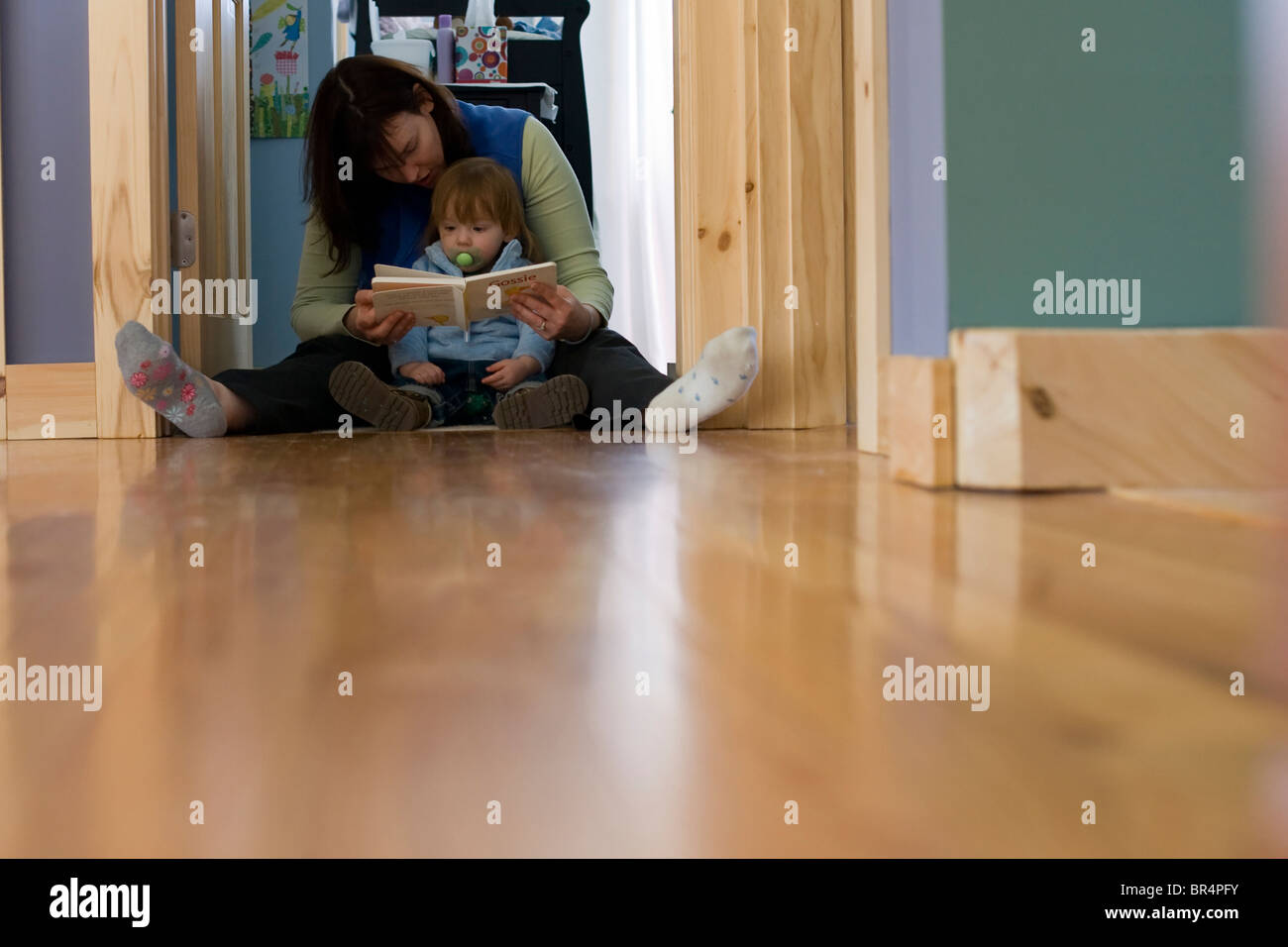 A mother reads a book to her toddler. - Stock Image